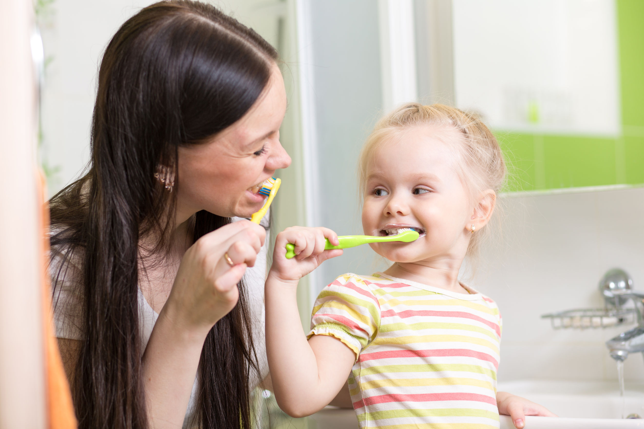 mom teaching child teeth brushing in bathroom